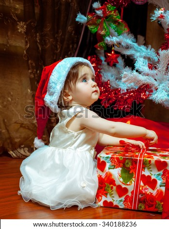 Cute little baby girl in Santa hat opens her first Christmas present. New year. Christmas mood. - stock photo