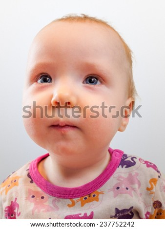 Cute little baby girl in studio shot. White background and cats in the shirt. - stock photo