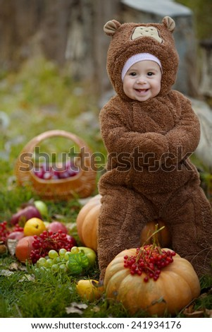 Cute little baby girl in the suit of bear in an autumn park - stock photo
