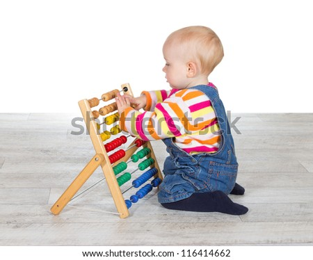 Cute little baby girl kneeling on the floor in dungarees playing with a colorful abacus moving the counters as she learns - stock photo