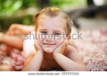 Cute little baby girl lying on a blanket in the park. Close-up portrait of child resting her head on her hands and looking into the camera. Shallow depth of field. Selective focus. - stock photo