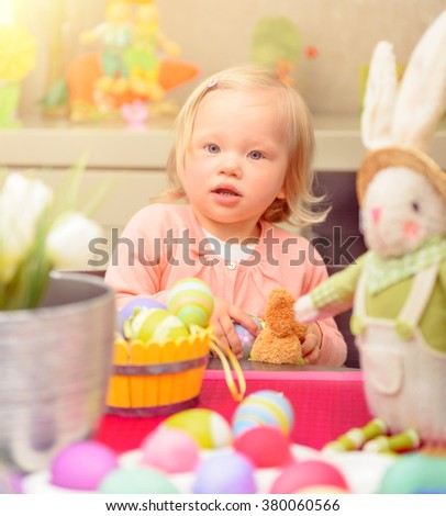 Cute little baby girl painting eggs in different colors near traditional Easter bunny, art lesson in daycare, celebrating happy spring holiday - stock photo