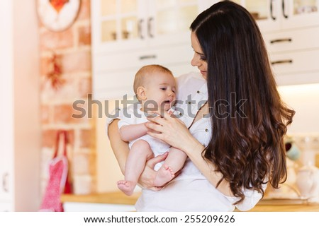 Cute little baby girl playing with her mother in a living room. - stock photo