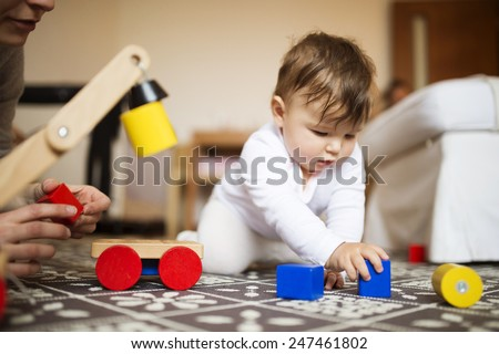 Cute little baby girl playing with her mother on a carpet in a living room. - stock photo