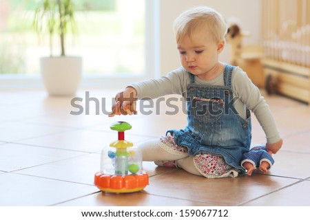 Cute little baby girl plays with toys sitting indoors on a tiles floor - stock photo