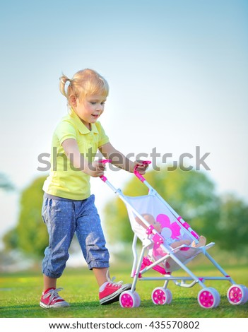 Cute little baby girl walking with pram outdoors, happy child with toys playing in the park on a bright sunny day, preschoolers daycare - stock photo