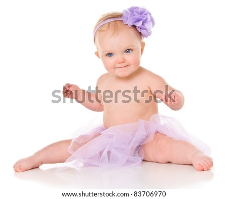 Cute little baby girl with big blue eyes wearing a tutu and flower in her hair - stock photo