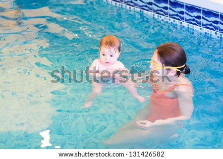 Cute little baby in an early swimming class - stock photo