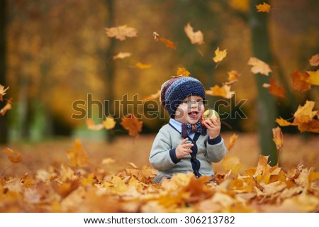 cute little baby in autumn park with yellow leaves - stock photo
