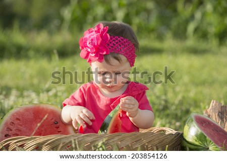 Cute little baby in basket playing with watermelon - stock photo