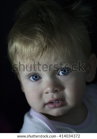 Cute little baby in low key with small amount light. Pretty children infancy and people age concept. Beautiful happy girl boy child face adorable portrait. Son daughter childhood. Wise expression kid. - stock photo
