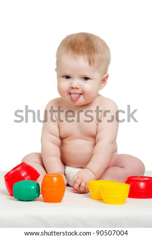 Cute little baby is playing with color toys, isolated over white - stock photo