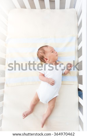 Cute little baby lying in white cradle at sunny day - stock photo