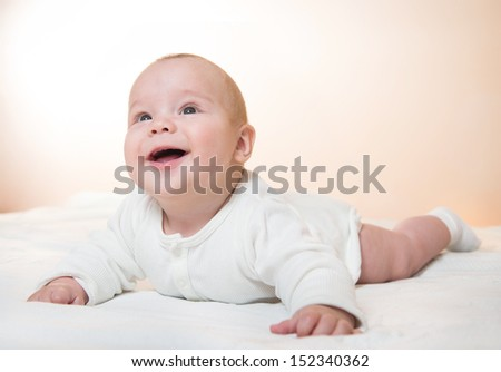cute little baby lying on bed, orange background