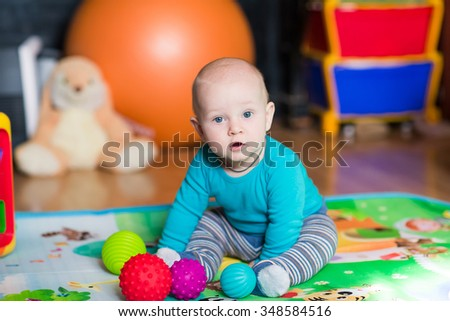 Cute little baby playing with colorful toys - stock photo