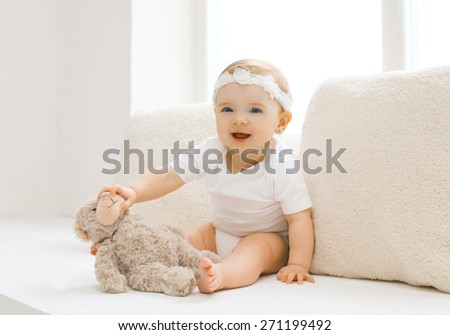 Cute little baby playing with toy at home in white room near window - stock photo
