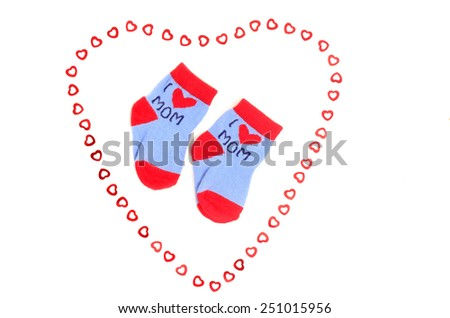 Cute little baby socks isolated on white. Small blue socks saying I love mom with heart. - stock photo