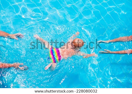 Cute little baby swimming underwater from mother to father in a pool, learning to swim lessons and early development concept - stock photo