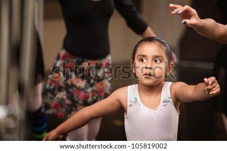 Cute little ballerina practicing in a dance studio - stock photo