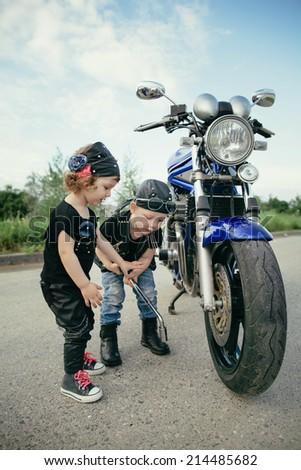 cute little biker repairs motorcycle on road  - stock photo