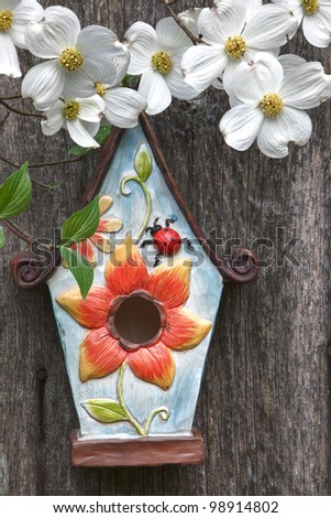 Cute little birdhouse on rustic wooden fence with beautiful white Dogwood blooms - stock photo