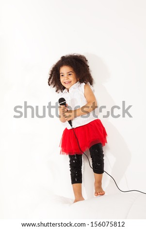 Cute little black African three years old girl with cute curly black hair with microphone performing standing on the coach and dancing - stock photo