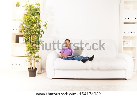 Cute little black boy sitting with laptop computer on the coach and typing in living room