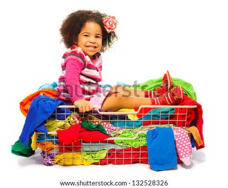Cute little black girl sitting in the basket full of clothes with fuzzy hair and smile on her face, isolated on white - stock photo