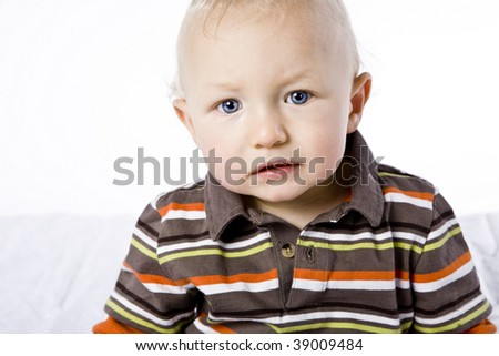 Cute little blond boy posing in studio.