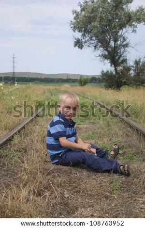 Cute little blond boy sitting on railway - stock photo