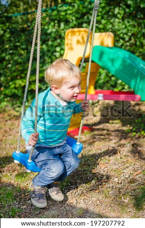 Cute little blond boy swinging on swings in the outdoor playground - stock photo
