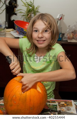 Cute little blond caucasian girl at home in the kitchen carving a pumpkin for Halloween - stock photo