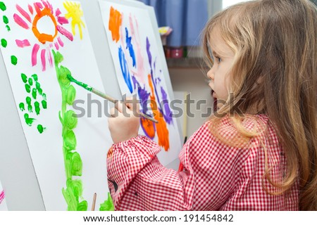 Cute little blond girl holding brush and painting on paper - stock photo