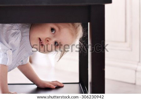 Cute little blond girl in striped shirt climbed in recess table - stock photo