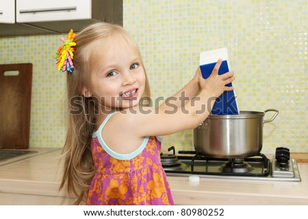 Cute little blond girl making soup  in the kitchen at home - stock photo