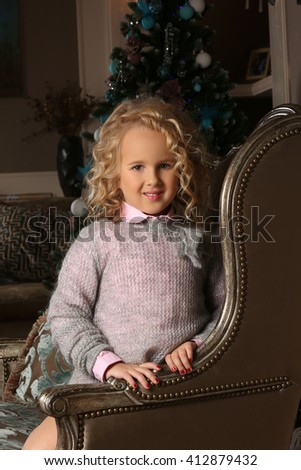 Cute little blond girl sitting peering over chair arms