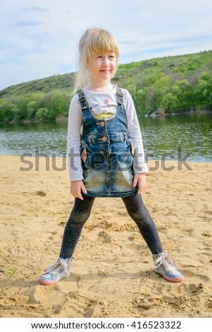 Cute little blond girl standing on a sandy beach in a denim skirt and leggings smiling happily as she looks to the side