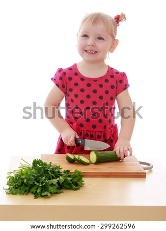 Cute little blonde girl in a red polka-dot dress standing in front of a cutting Board and cut with a knife cucumber, next on the table are fresh vegetables-Isolated on white background - stock photo