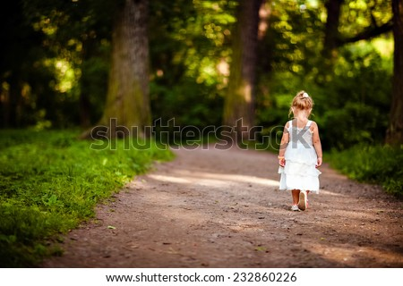 cute little blonde girl in a white dress walking down the path in the forest, the view from the back - stock photo
