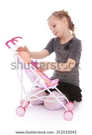 Cute little blonde girl playing with a doll . The girl puts the doll to sleep in the stroller - Isolated on white background - stock photo