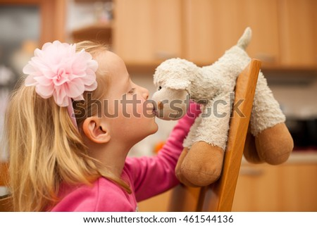 Cute little blonde girl plays with sheep toy