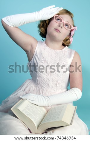 Cute little blonde girl reading a book - stock photo
