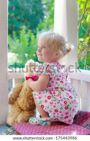 Cute little blonde girl, wearing a sweet summer dress, sitting on a veranda outside her home with a teddy bear in her arms. Wonderful light and summery mood. - stock photo