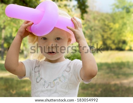 Cute little blonde girl with a serious expression wearing a pink hat made from a twisted and tied balloon with her hands raised holding it on - stock photo