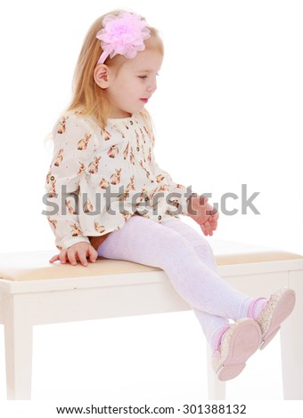 cute little blonde girl with pink bow on her head sitting on a white couch. Girl dressed in a white blouse and brown shorts.-Isolated on white background - stock photo