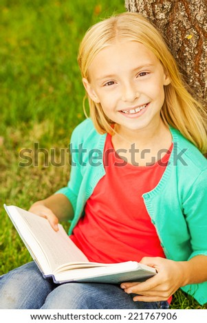Cute little bookworm. Top view of cute little blond hair girl holding book and smiling to you while sitting on green grass and leaning at the tree  - stock photo