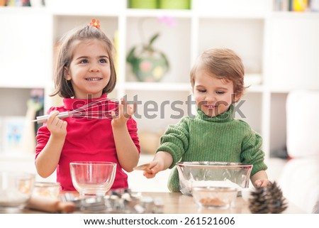 Cute little boy and girl having fun playing in the kitchen - stock photo