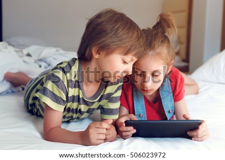 Cute little boy and girl playing with tablet on bed