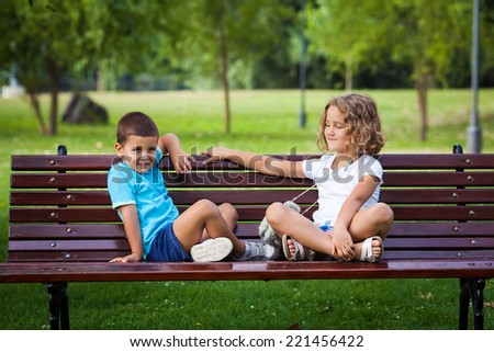 Cute little boy and girl sitting on a bench in nature - stock photo