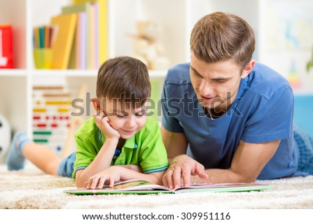 cute little boy and his dad read book together - stock photo